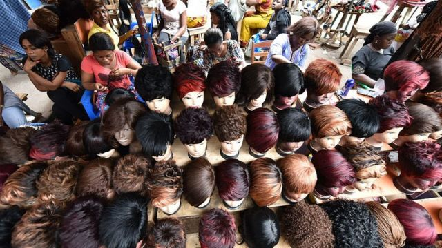 Women dey make wigs with artificial hair for one wig shop for market for Abidjan, Ivory Coast