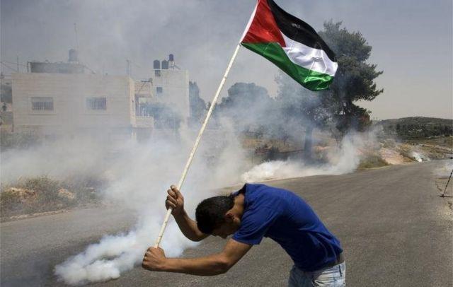 Un palestino sostiene su bandera entre gases en Nabi Saleh (foto de archivo)