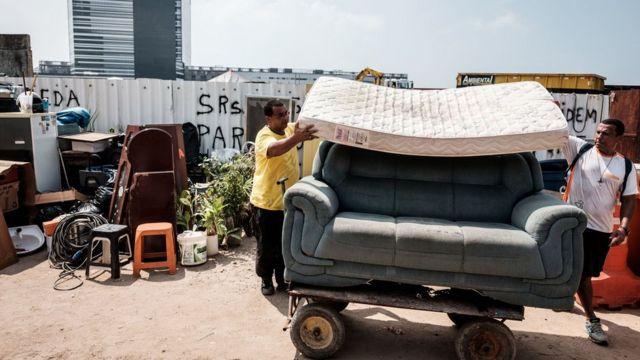 Dos residentes de Vila Autódromo mueven sus muebles en una carretilla