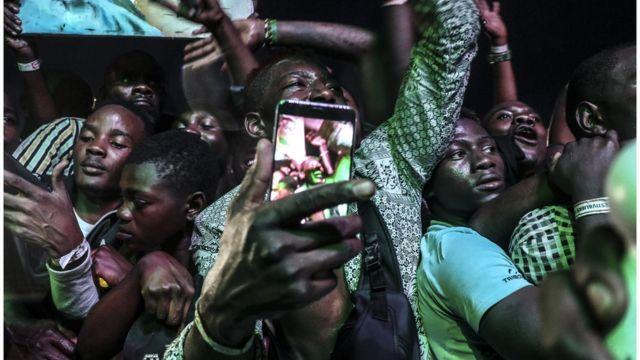 Un jeune se prend en photo dans la foule.