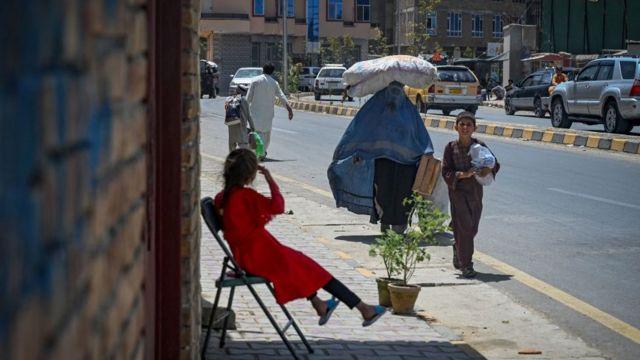 امرأة ترتدي البرقع وتحمل كيسًا على رأسها تمشي على طول طريق في كابول في 7 أغسطس 2021