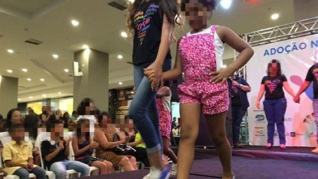 Duas crianças de diferentes idades desfilam em passarela, assistidas por plateia