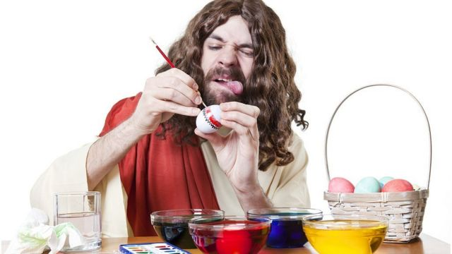 Man trying to paint an egg with his tongue out