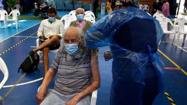 Personas recibiendo la vacuna en un gimnasio en Chile.