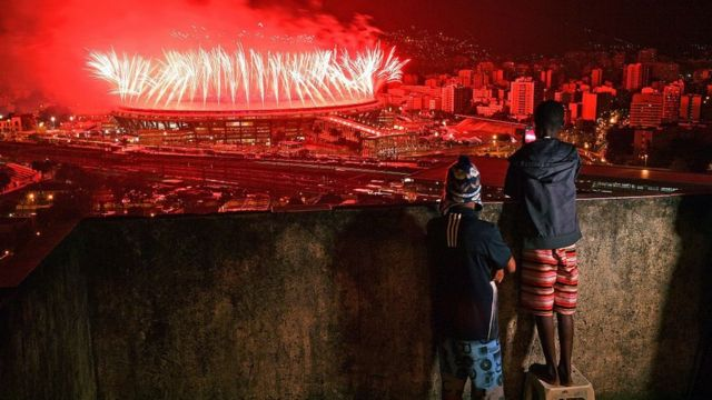 Children from Mangueira favela watch fireworks over Maracana Stadium during the Rio 2016 Olympics Games closing ceremony in Rio de Janeiro on August 21, 2016