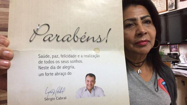 Zoraide mostra cartão com uma fotografia sorridente do ex-governador Sérgio Cabral, desejando-lhe parabéns