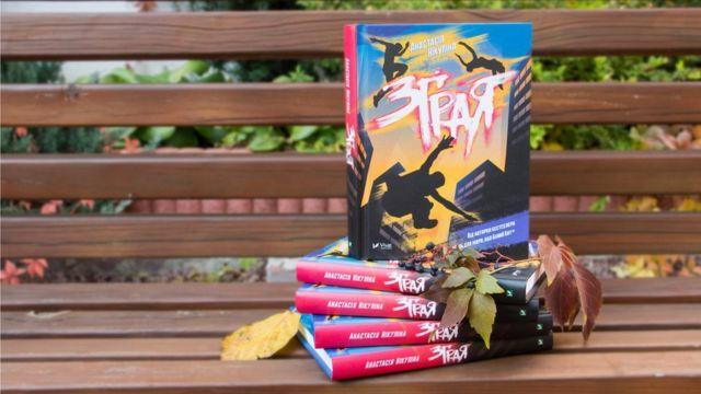 "Книга ""Зграя"" на лавці з листям"
