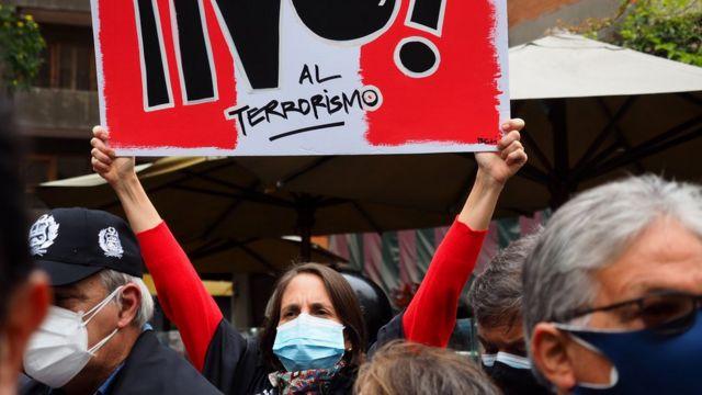 """Mujer porta un cartel con el mensaje de """"No al terrorismo""""."""