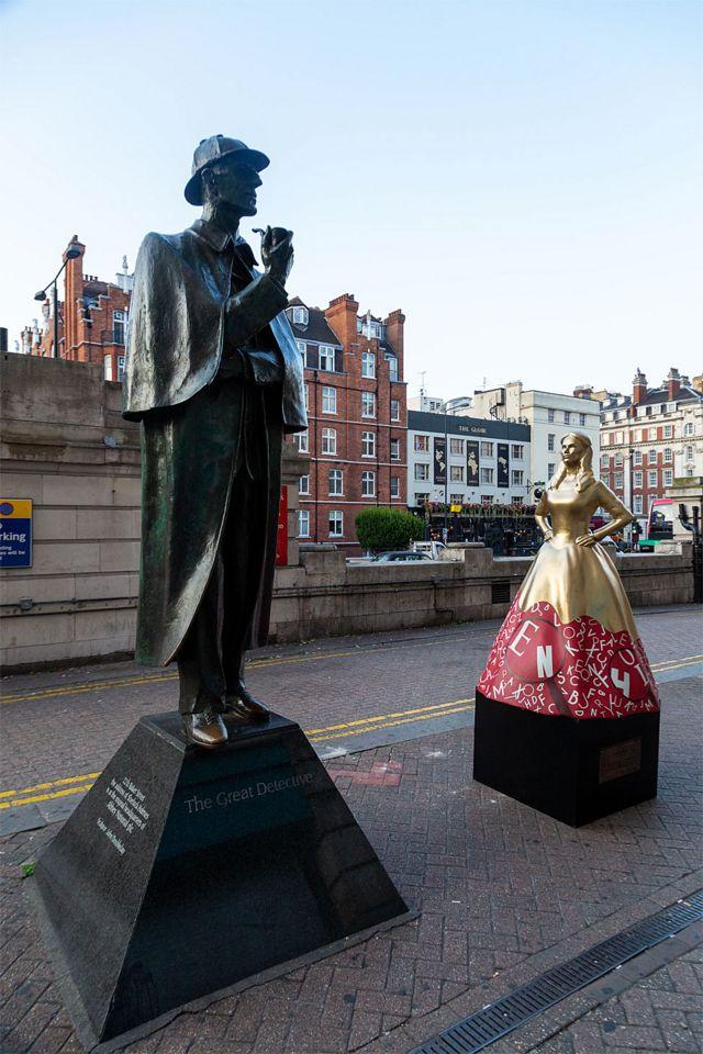 Enola em frente à estátua de seu irmão Sherlock Holmes