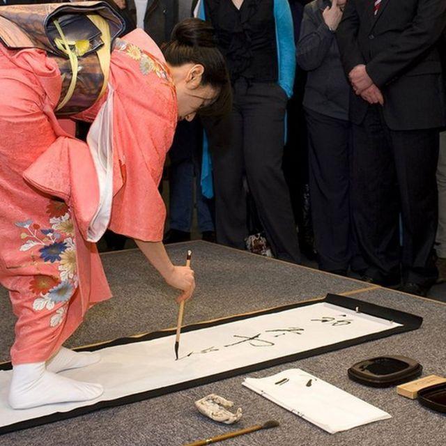 mulher escreve em papel no chão