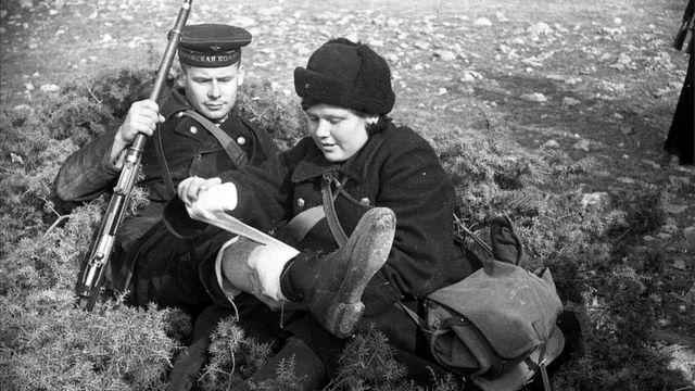 Медсестра оказывает помощь раненому краснофлотцу, на ногах которого ботинки, присланные по ленд-лизу, 1942 г.