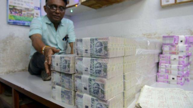 दो हज़ार और एक सौ रुपए के नए नोट के साथ एक व्यक्ति.
