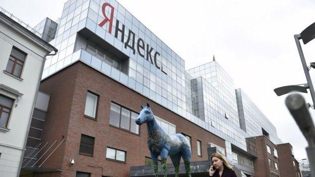 Женщина говорит по телефону возле главного офиса Яндекса в Москве, 16 мая 2017 года