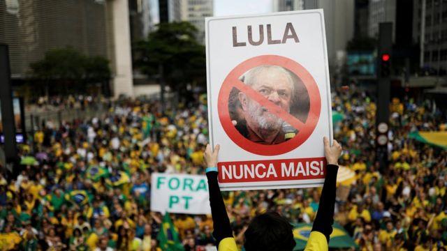 """Manifestante segura placa """"Lula nunca mais""""; ao fundo, manifestação em apoio a Bolsonaro, com pessoas vestidas de verde e amarelo"""