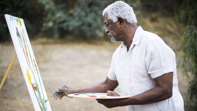 Un hombre pinta un cuadro.