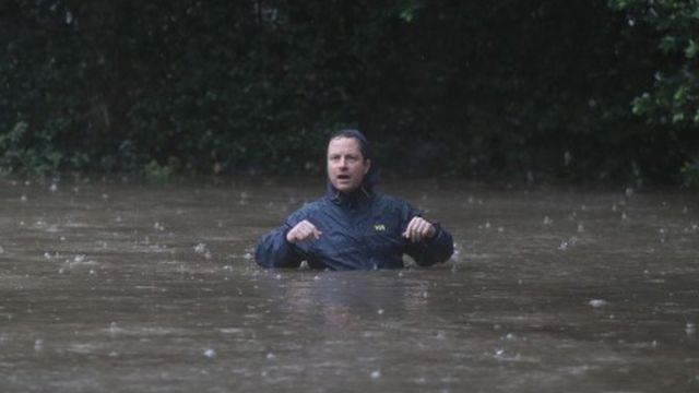 Qof dadka deegaanka ka tirsan oo dhex socda biyo daad ah xaafadda River Oaks ee Houston oo ay qaadeen daadadkii ka dambeeyey duufaanta Harvey, 27 Agoosto.