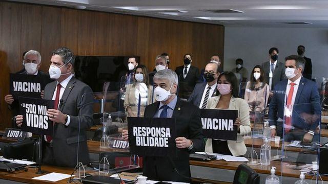 """Senadores exibem placas que diz: """"+ de 500 mil vidas""""; """"Responsabilidade""""; """"Vacina""""."""