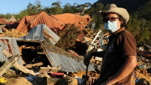 Homem em frente a casa destruída