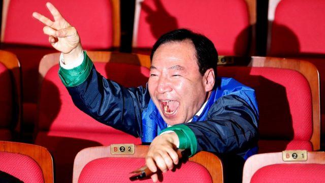 選挙結果に喜びの表情を見せる「共に民主党」の党員(13日、ソウル)