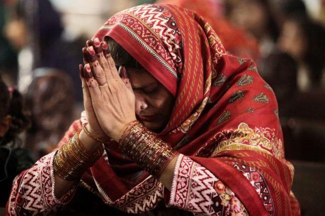 Женщина молится во время рождественской службы в соборе Святого Сердца в Лахоре, Пакистан