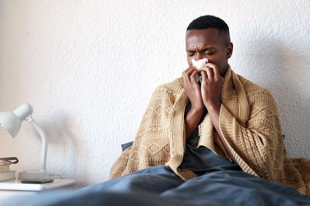 Um homem na cama assoando o nariz