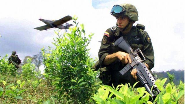 Un soldado colombiano avanza en un cultivo de coca de la zona de Nariño mientras un avión arroja pesticidas.