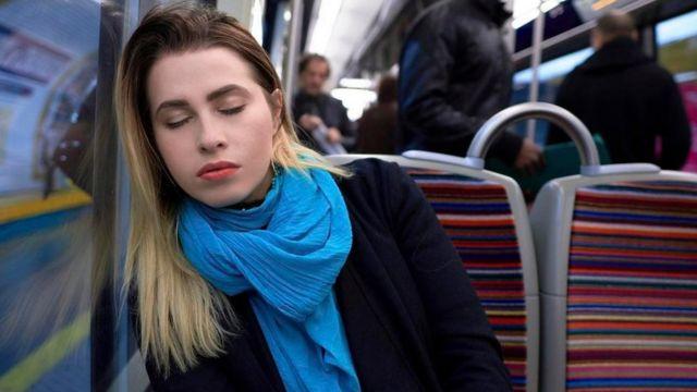 Una joven dormida en un tren del metro