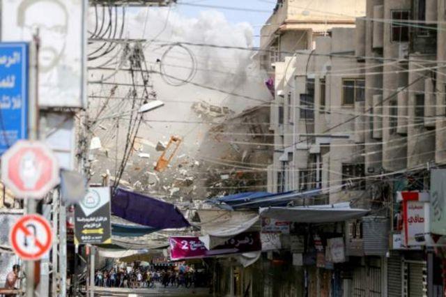 İsrail'in Perşembe günü Gazze'ye gerçekleştirdiği hava saldırısında bazı binalar yıkıldı