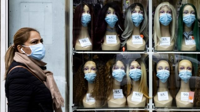 Une femme portant un masque de protection passe devant une vitrine affichant des têtes de mannequin avec des masques à Paris, France, 28 octobre 2020