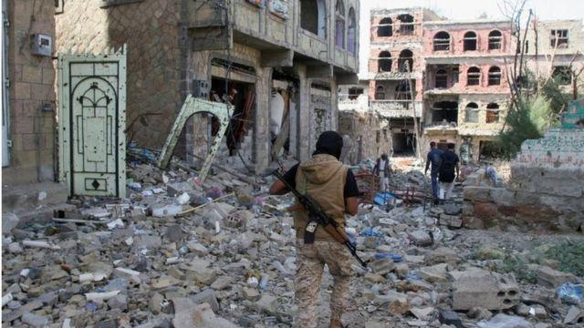 أشخاص يسيرون وسط الحطام في اليمن