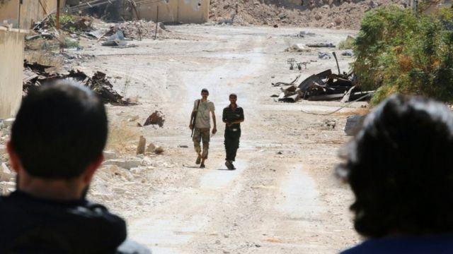 Militantes de grupos rebeldes caminan en Alepo.
