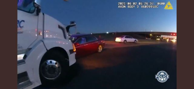 A white lorry that has crashed into a red car, a still from a body cam video