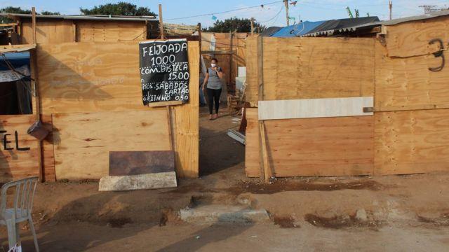 Construção com tapumes de madeira e placa anunciando feijoada a R$10