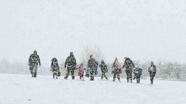 Люди гуляют под снегом