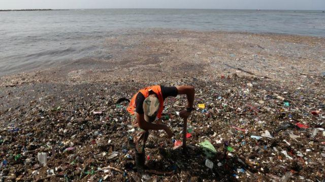 Hombre trabajando en la limpieza de basura en las playas del Malecón de Santo Domingo, República Dominicana.