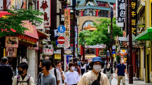 People wearing face masks visit the Chinatown area in Yokohama on May 26, 2020.