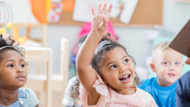 Imagem mostra menina com o braço levantado junto a outras crianças na escola