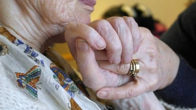 Woman with Alzheimer's disease holding hands with a carer