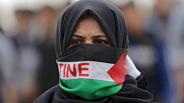 демонстрантка с завязанным палестинским флагом лицом