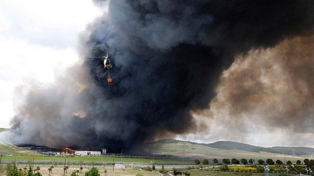 A helicopter prepares to drop water over the fire