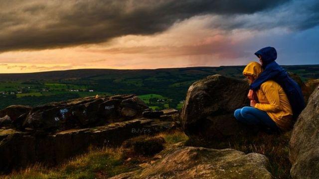 شخصان ينتظران عاصفة على تل