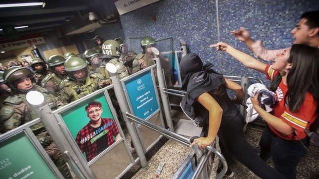 Jóvenes enfrentados a carabineros en el metro de Santiago de Chile