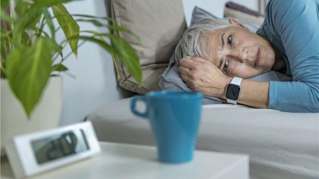Una mujer acostada que parece que no puede levantarse.