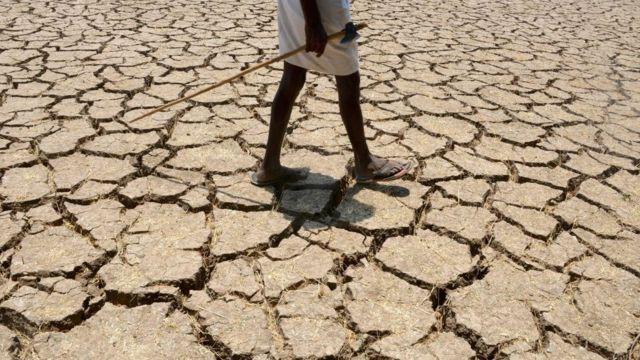 Un niño camina sobre un terreno árido