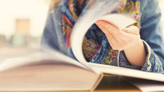 Mujer pasa hojas de un libro.