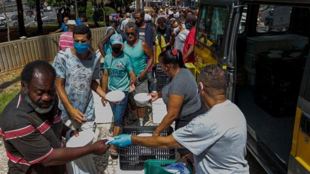 Moradores de rua recebem almoço no centro de São Paulo, Brasil, em 23 de março de 2021.