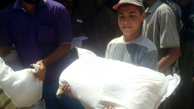 Niño refugiado con un saco de alimentos