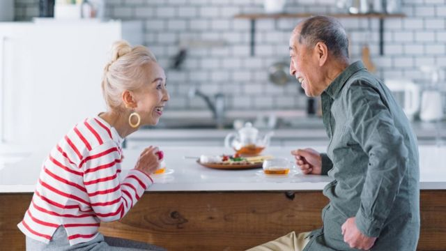 A woman and a man sit and speak face to face at a breakfast bar