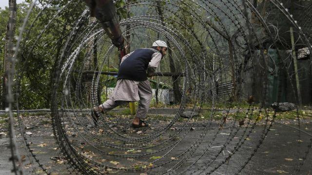 उड़ी में सेना के शिविर पर हमले के बाद सड़क पर लगे कंटीले तारों से होकर गुजरता एक व्यक्ति.
