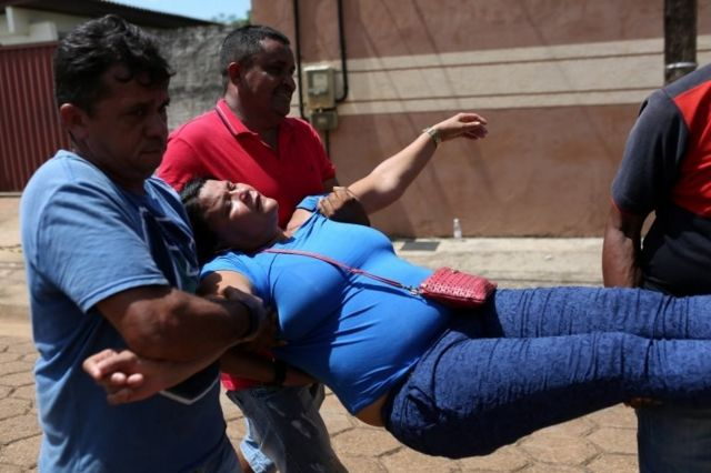 A relative of a prisoner is carried away after she fainted in front of the Medical Legal Institute of Altamira, Brazil, July 30, 2019